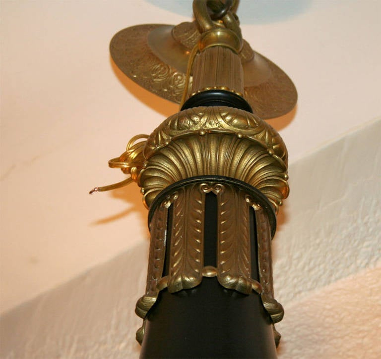 A late 19th century French Empire style chandelier with gilt and painted finish.  Measures: Height 42 in. diameter 38 in.