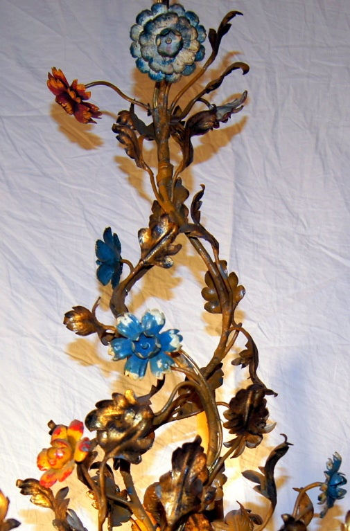 A circa 1930 gilt metal Italian chandelier with 3 lights, with painted flowers in reds, blues and yellow. Original patina.