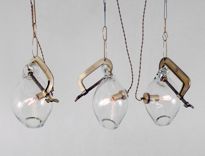 A collection of old industrial clamps from manufacturers across the United States that are then plated in brass.  Adelman's  glassblower, Michiko Sakano, blows molten glass into each one and lets the form naturally slump, making each fixture truly