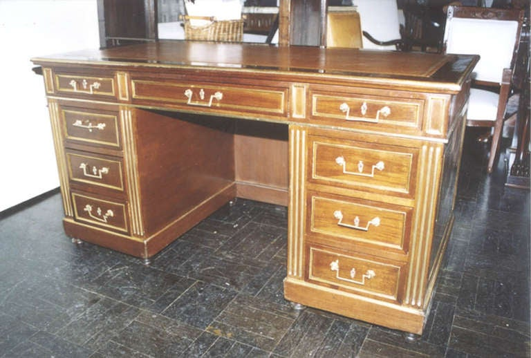 19th century mahogany pedestal desk, cognac leather top with pull-out writing slides above, three short drawers below on either side, all fitted with brass handles and molded brass borders flanked by fluted pilasters, bun feet.