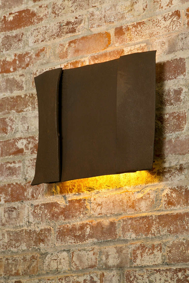 Sculptural steel wall sconce. This is a unique wall sconce and while more are available, each one will be individually made with its own historical characteristics.