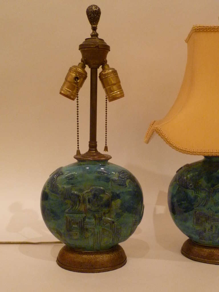 REDUCED FROM $4500....Wonderful pair of Wiener Werkstatte table lamps of hand glazed pottery vases by Vally Wieselthier featuring a moon shaped form with a stylized floral design in relief, mounted on bronze bases with a repeating oak leaf