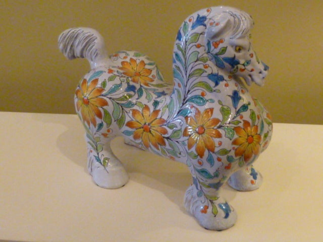 Midcentury and magnificent! This Italian ceramic horse is instantly a favorite with its big broad draft horse shape entirely decorated in relief and in vivid colors, fantastic flower forms. A very friendly mystical beast, beautifully realized. A