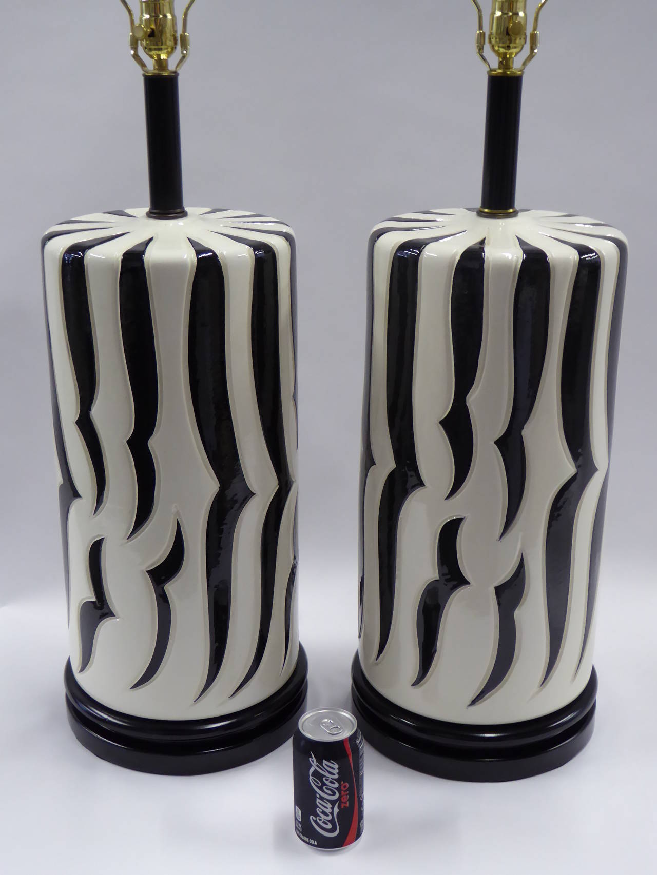 Exhibiting the exotic and luxe exuberant style of Tony Duquette, this pair of monumental scale table lamps with stylized incised zebra stripes has a wonderful presence and scale. As important room anchors, the black and white quite graphic. The