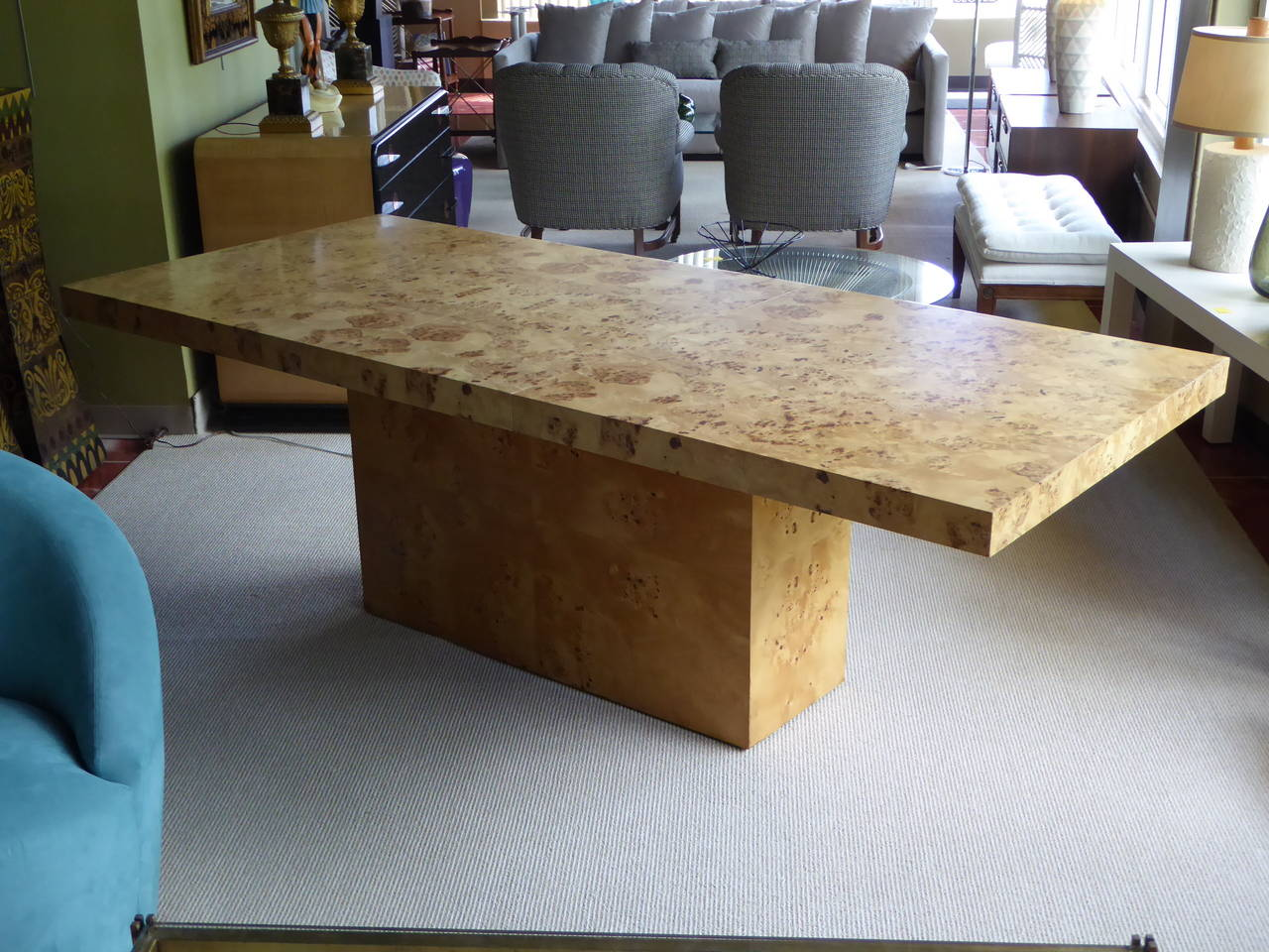 "Beautifully modern with strong simple lines, this olive burl wood dining table makes a statement. Wonderfully figured woods add exotic flair. Has one 18"" extension leaf that stores inside base. Very good condition with minor rub area on one corner."