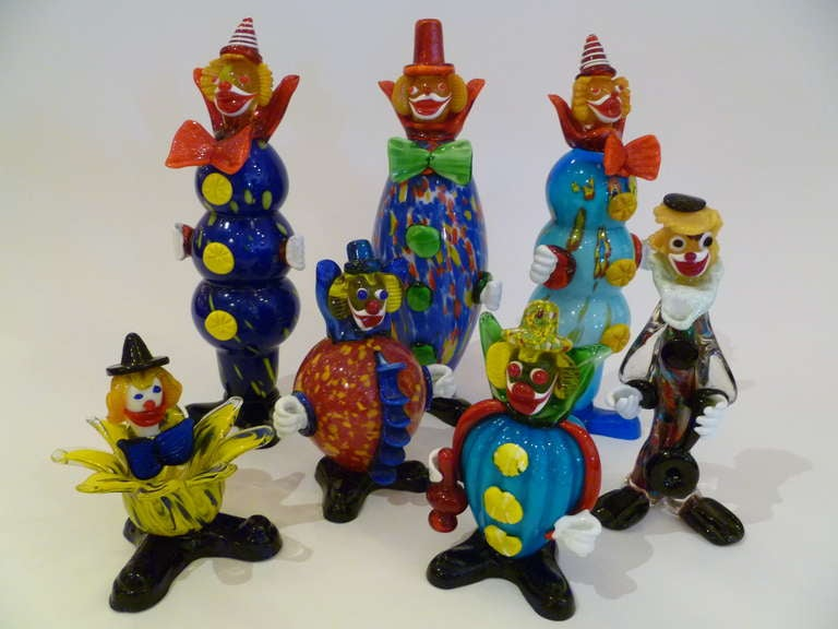 An instant collection and such fun with this grouping of seven midcentury Murano glass clowns in a riot of color and form. Happy faces and costumes, they include three tall fellows and four more varying in height and dress. Several retaining gold