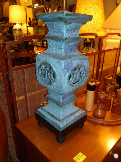 Impressively large and beautifully regal, this tall James Mont style table lamp has a bubbly lava glaze of teal blue with varied shading from darker blue to gray. An imposing oriental newel or garden lantern shape, the centered design is pierced and