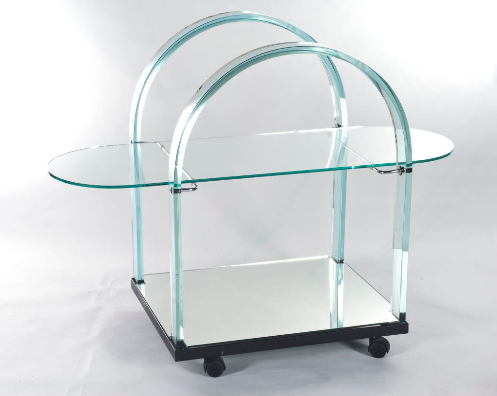 Bar cart of glass and mirror. Beautifully curved arms with a glass tableau and mirrored bottom shelf.