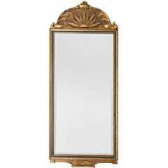 Gilt wood Swedish Art Deco mirror with sunburst and oil lamp motif.