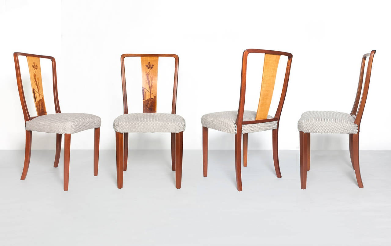 Scandinavian Modern group of four solid mahogany dining chairs with back panels veneered in walnut, elm root, rosewood and birch marquetry, Designed by Erik Chambert, made at Chambert's furniture company, Norrkoping, Sweden, late 1930s early 1940s.