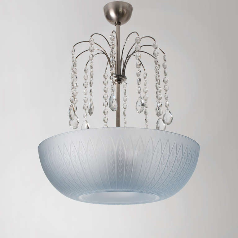 Swedish art deco pendant with light blue etched glass shade by Simon Gate for Orrefors. The center stem has 12-arms holding strings of clear cut crystals. The metal has a nickel finish as well as the canopy and finial. Newly rewired with three