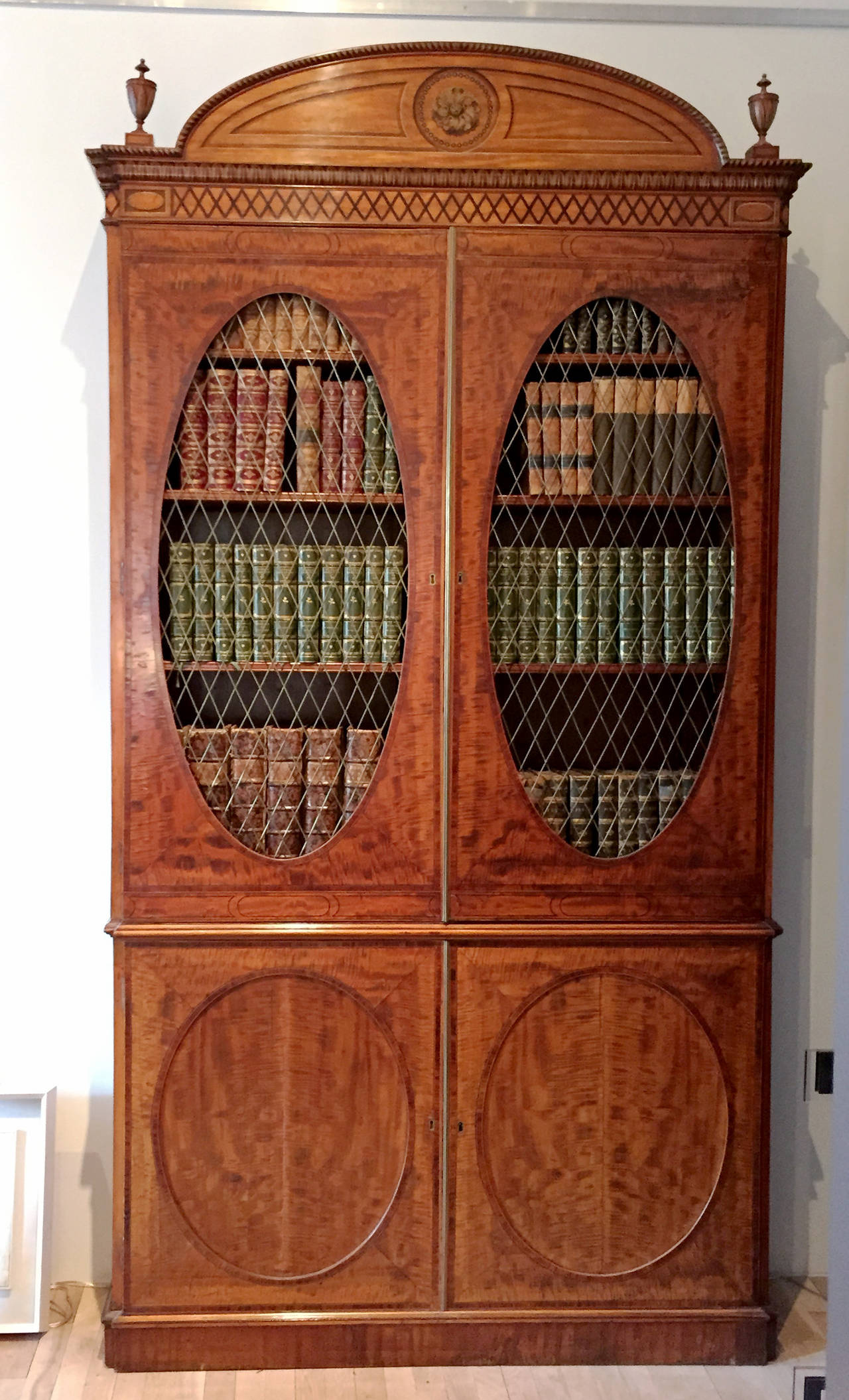 A very fine Hepplewhite decorated inlaid satinwood and mahogany two-part bookcase cabinet, English, circa 1785. Provenance: The Estate of Mary Knowles (Polly) Wisner Fritchey of The Georgetown Ladies Social Club, Washington, D.C. Literature: F.