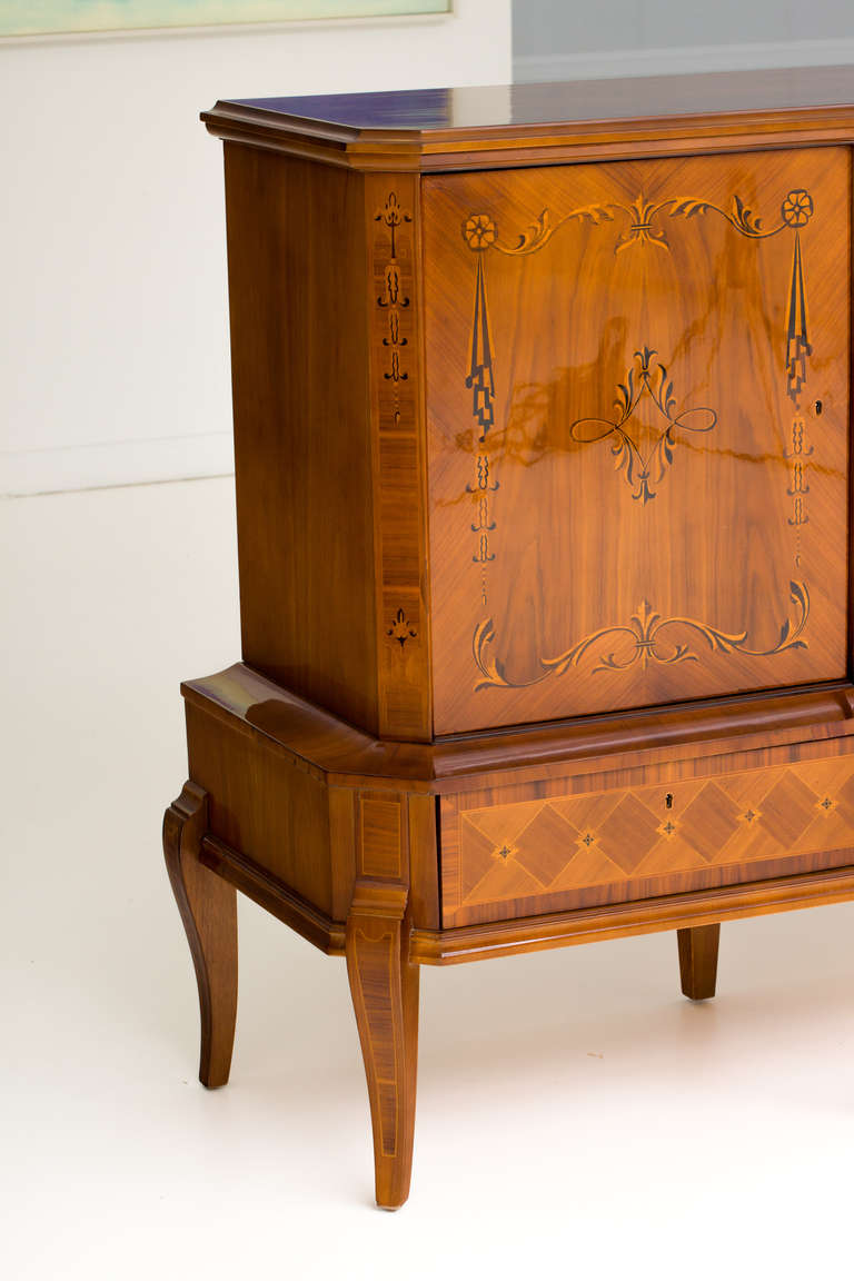 Exquisite Hungarian Art Deco walnut sideboard with exotic wood inlays consisting of ebony, lemonwood and Macassar. Sideboard features three compartments with adjustable shelves and bottle rack. Four drawers below the compartments provides ample