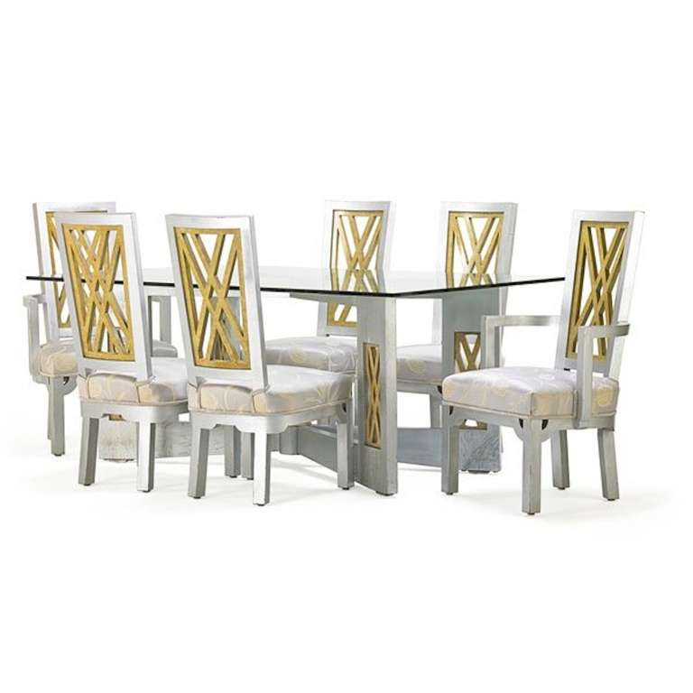 Fantastic 1960s Chinoiserie influenced dining set in silvered and gilded wood with polychromed details. Set includes four side chairs and two arm chairs with gilded fretwork backs and a stately dining table with a glass top. In fantastic original