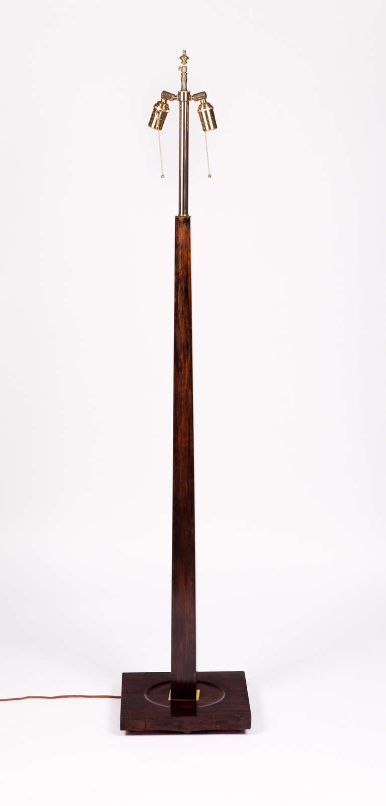 Exceptional tapering column floor lamp composed of one piece of solid Macassar ebony with brass hardware. Rewired with silk cord and double sockets.