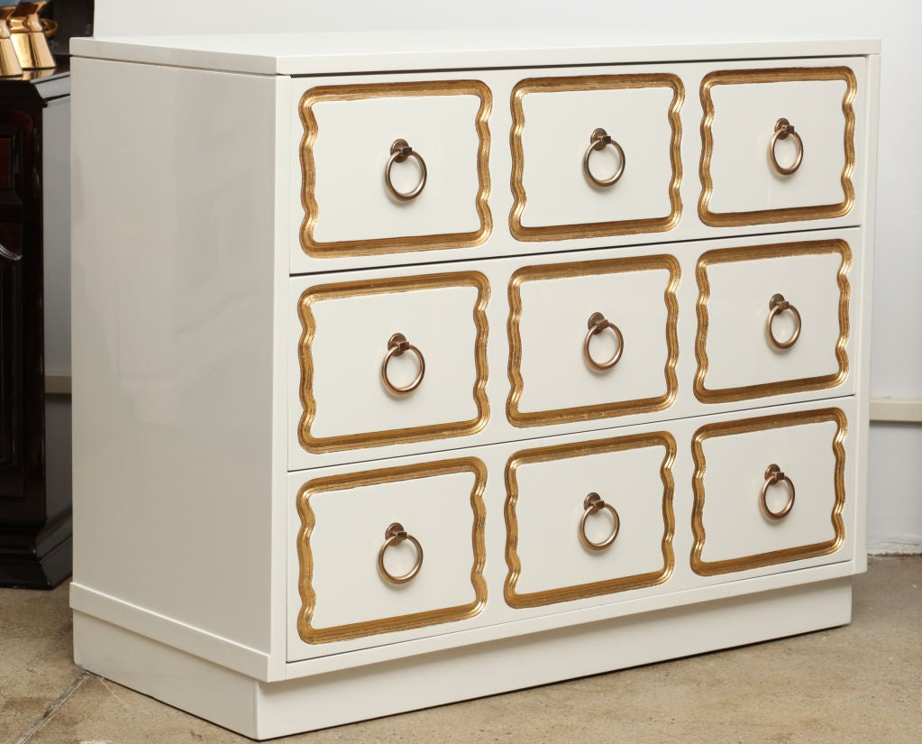 Exceptional 3 drawer chest of drawers in a high gloss white lacquer with carved and gilded drawer fronts and satin brass pulls.