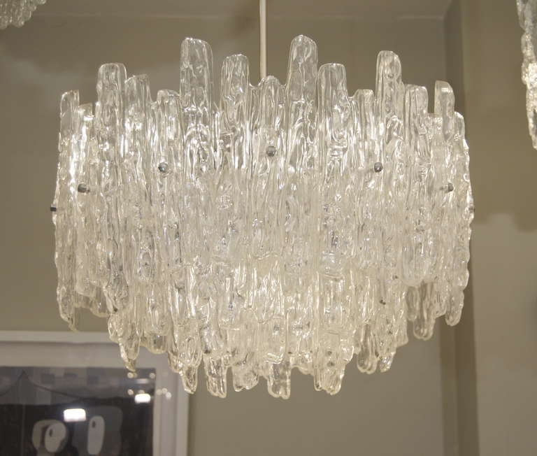 Excellent and large chandelier in the style of Kalmar ice glass, with substantial lucite pieces in three tiers. Transparent lucite. Dramatic, large, and a statement piece.