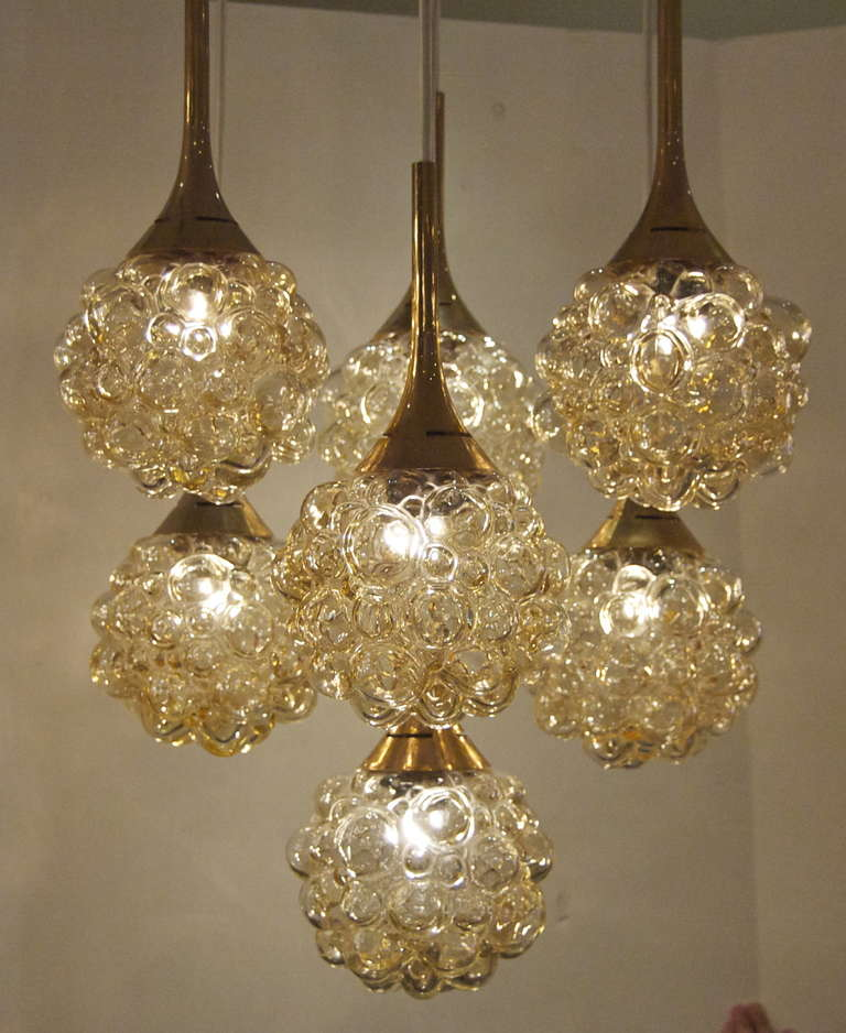 Beautiful chandelier comprised of seven amber tone bubble glass pendant bodies, with brass-tone accent hardware.  Takes seven E-14 base bulbs up to 40 watts per bulb, new wiring. Total height can be adjusted as required.