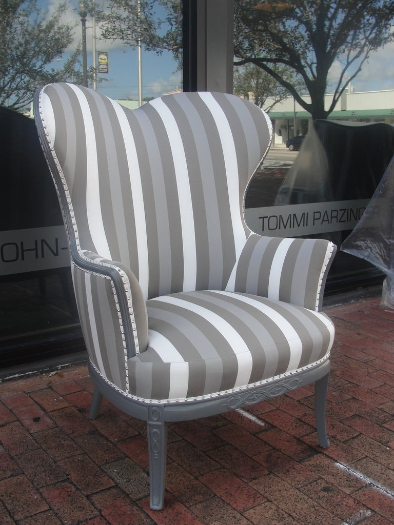 """Description: There is a pair we are calling the """"King and Queen chairs"""" which feature the same elegant striped canvas fabric in grey tones. Lacquered grey and finished with chrome nail heads all around. Work great as host and hostess chairs or for a"""