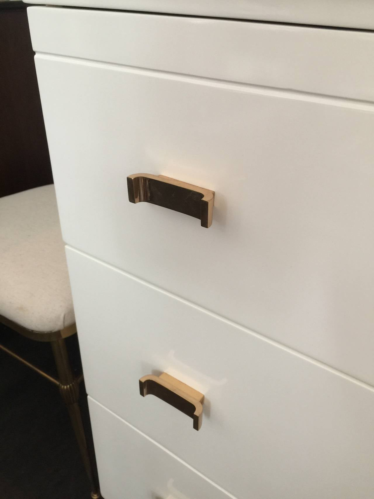 Manufactured and labelled by Amodec, this important Art Deco piece displays simple lines and elegant polished bronze hardware. Original ivory lacquer.