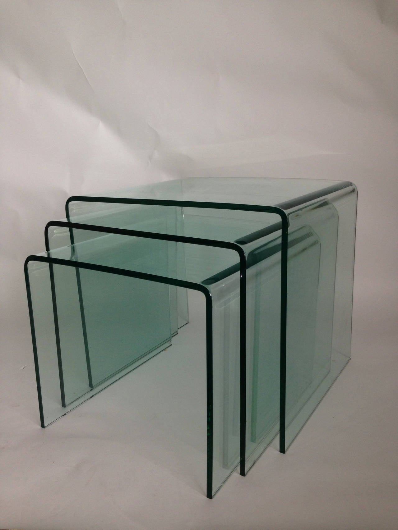 Made of tempered green glass, these nesting tables are wonderful together or apart.  Smaller table:  16 height, 17.5 wide, 19.75 deep