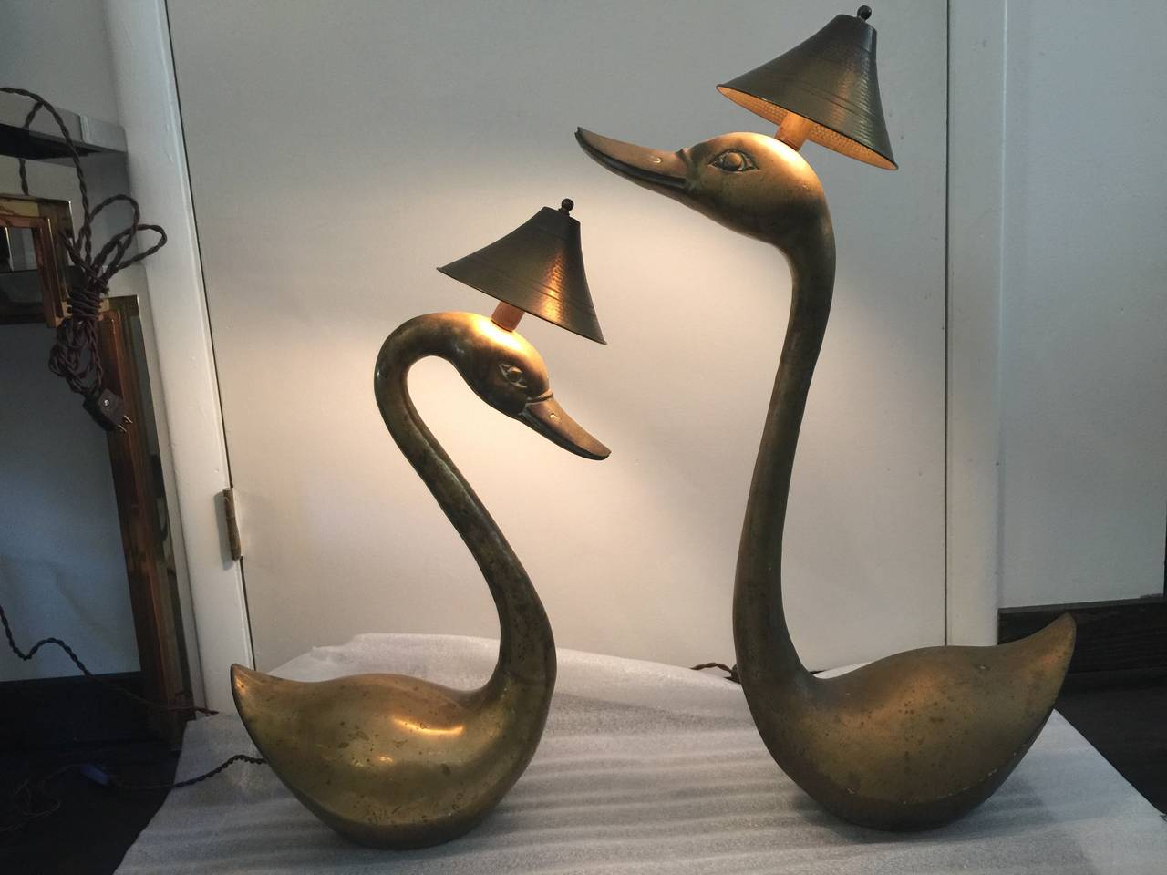 Wonderful scale sculptural brass lamps with metal shades. Wired with silk cords. Smaller lamp is 26