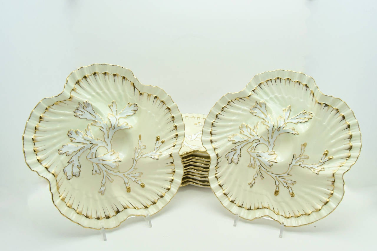 This unique set of 12 Aesthetic Movement, Brownfield's for Tiffany, oyster plates features a delicate shaped edge reminiscent of scallop shells with a coral design at the center to complete the nautical look. The gold trim over ivory, highlights the