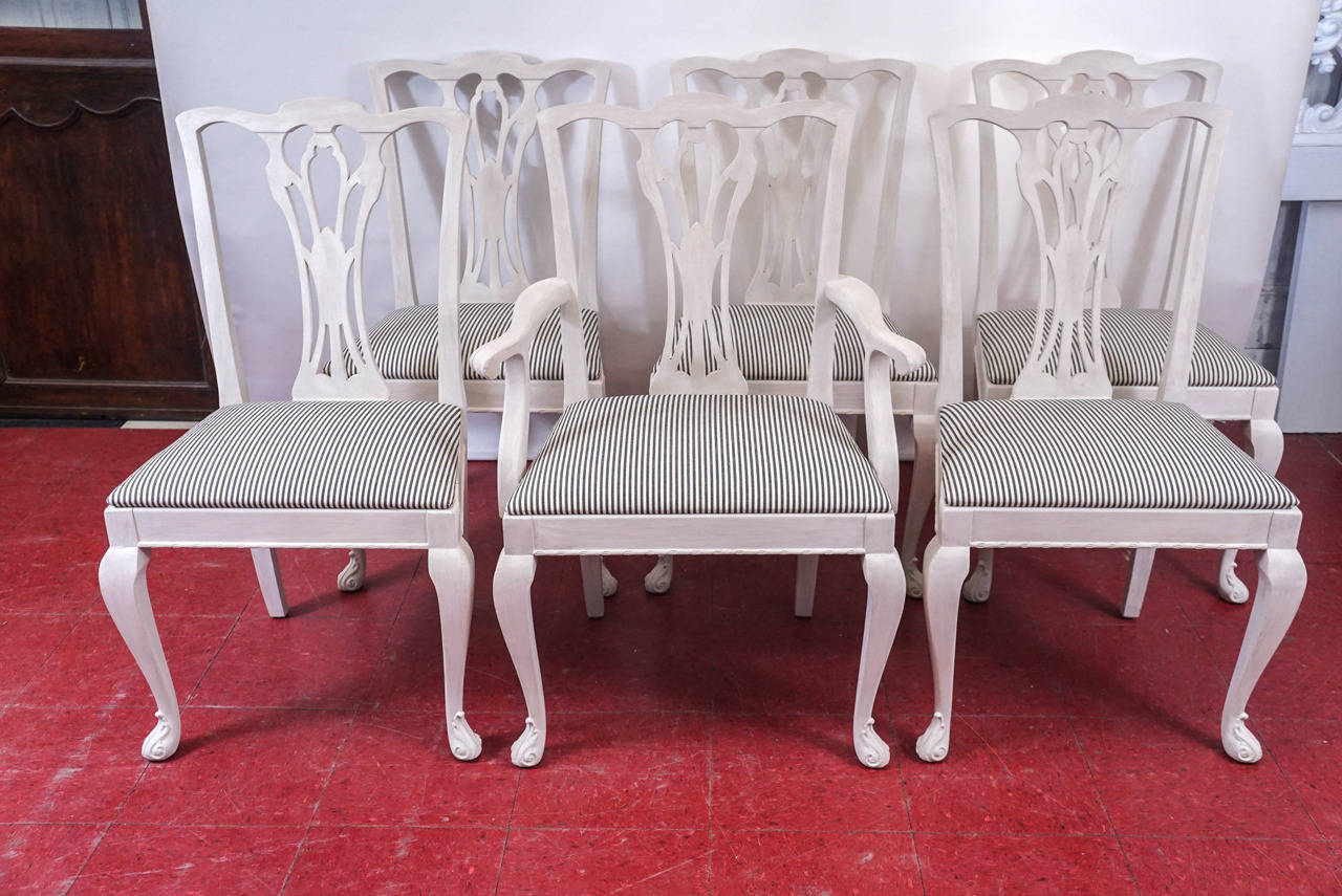 The six elegantly carved chairs are composed of five side and one arm, all newly painted in cream. The frames are secured by angled blocks at all corners. The padded pop-out seats are upholstered in new cream and black stripe cotton