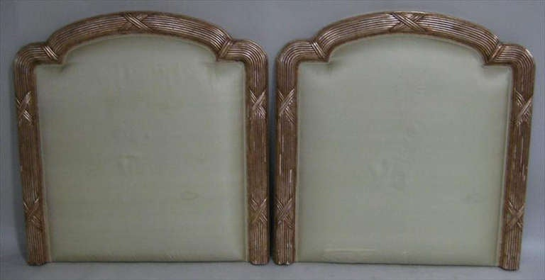 Pair of twin-sized upholstered and gilded headboards with molded and reeded frames.  We can raised to height of the headboard to your specification.