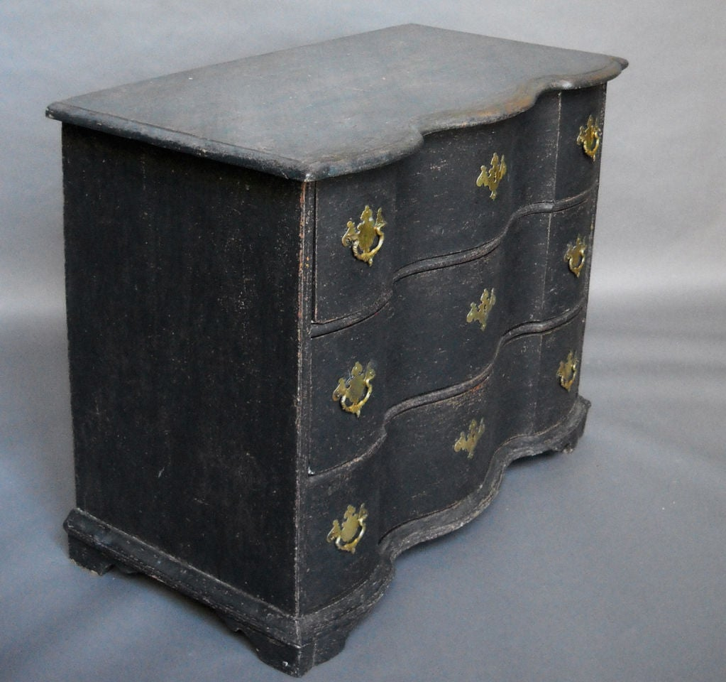 Chest of three drawers, Denmark circa 1750, with serpentine drawer fronts, shaped top, and bracket base. The hardware and painted surface are original.