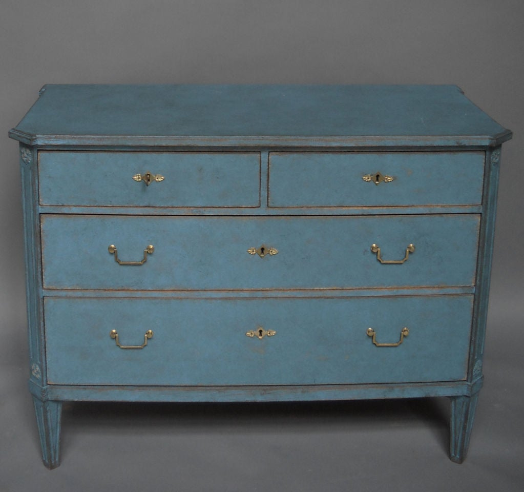 Gustavian style commode with two over two drawers, Sweden circa 1910, in secondary blue paint. Canted and fluted corners with applied rosettes and shaped top. Square tapering legs. Original brass hardware.