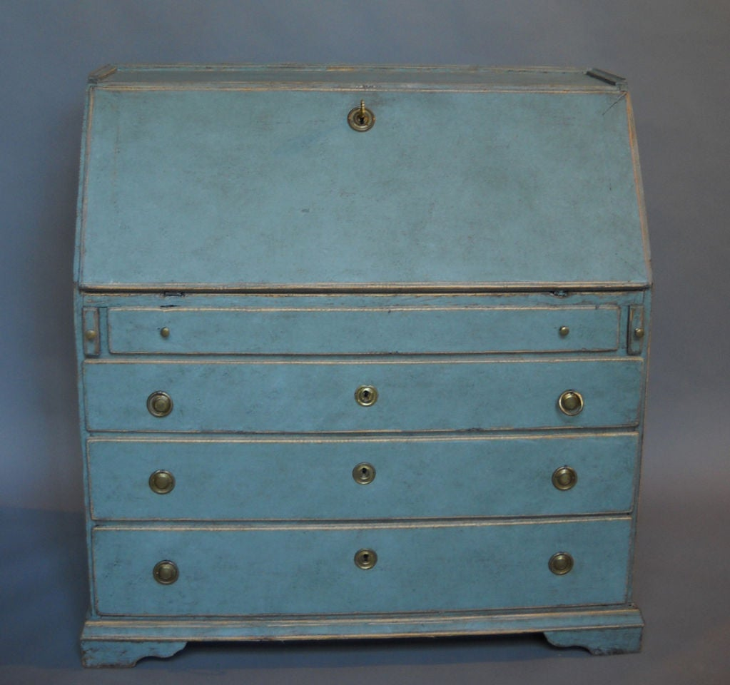 Swedish writing desk, circa 1820, with four graduated drawers under the slant-front. The interior features a central cupboard with lozenge trim and two banks of three drawers on either side. Great patina on the secondary blue paint.