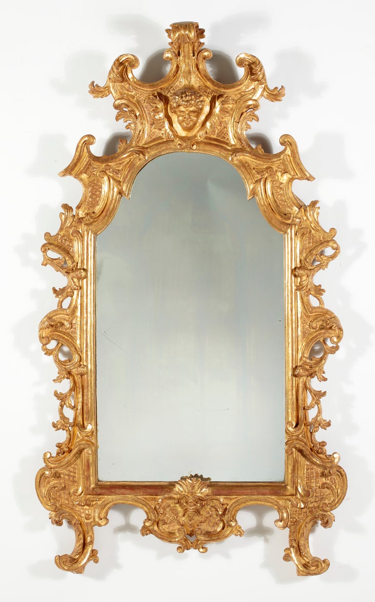 A Fine Rococo Giltwood Mirror Italy 18th Century  The oblong arched mirror plate within a molded frame carved with C-scrolls and foliage, surmounted with an elaborate crest with a face above and a central mask below  Height 61 in.  Width 37