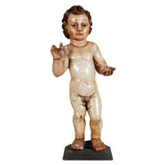 An Italian Carved Polychromed Figure of a Putto