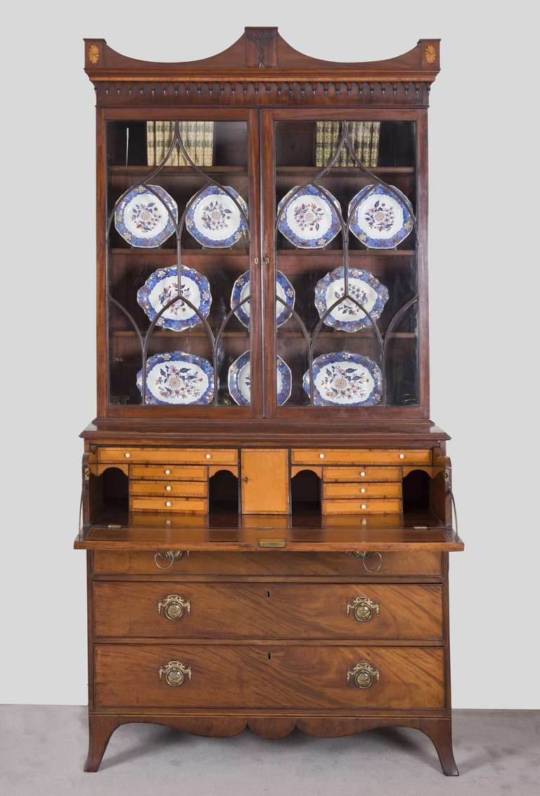 A fine quality George III mahogany library secretaire bookcase, the classical arch-molded cornice with central carved wheat sheath flanked by satinwood shell inlay at the corners, above two astragal-glazed doors opening to reveal three adjustable