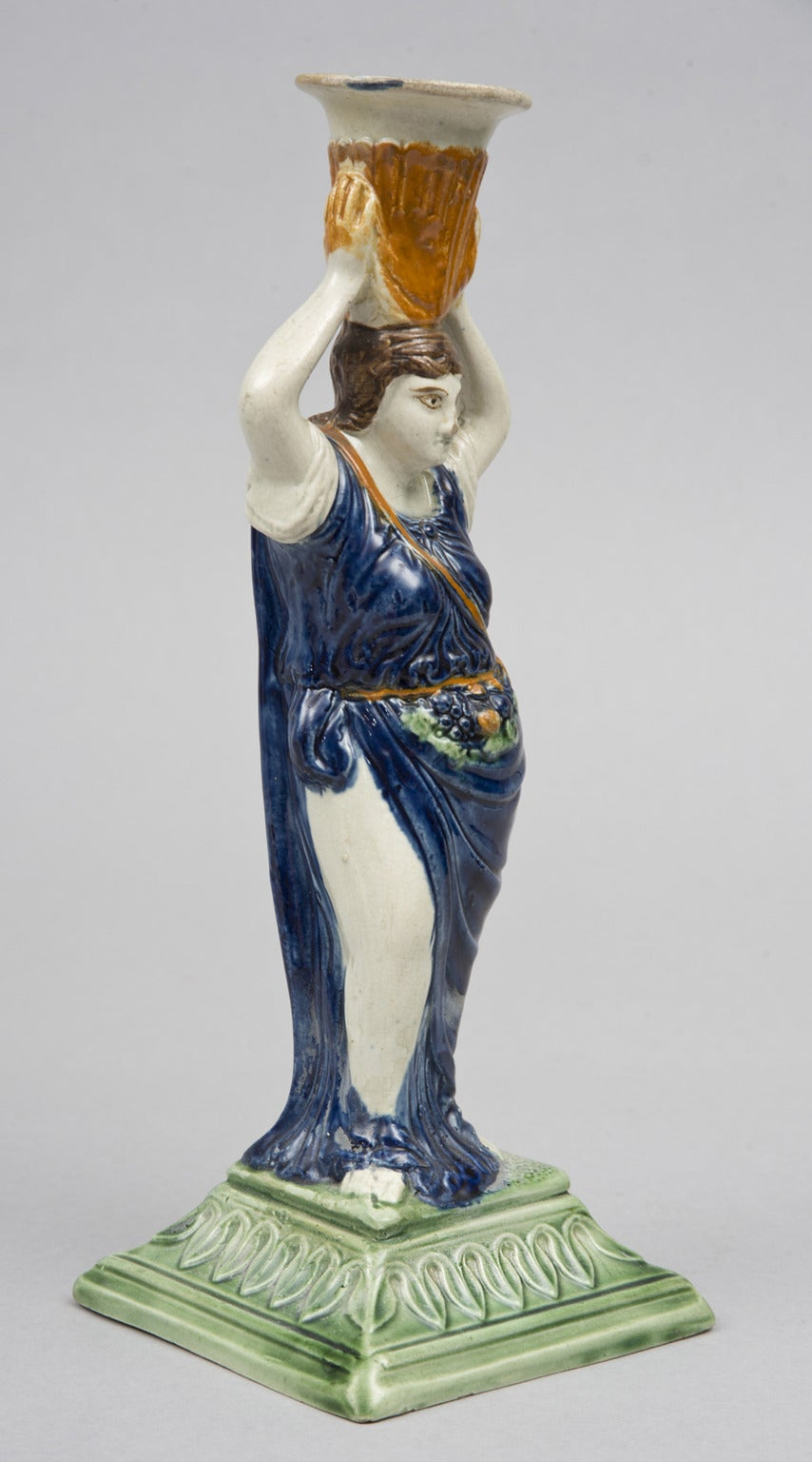 Prattware underglaze pottery candlestick of a classical female figure of summer wearing flowing blue drapery, carrying a pouch of fruit around her waist, holding an urn as a candle cup on her head, mounted on a green tapered square base decorated