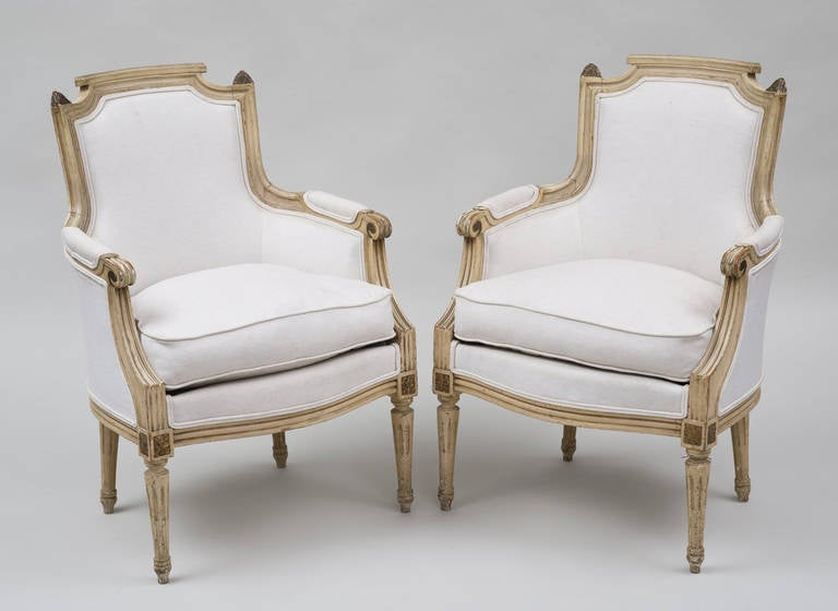 Pair of crème painted Louis XVI style beechwood bergères, molded frame with parcel gilding, carved hand rests, fluted arm supports and legs, padded arm rests, upholstered in off-white linen fabric.