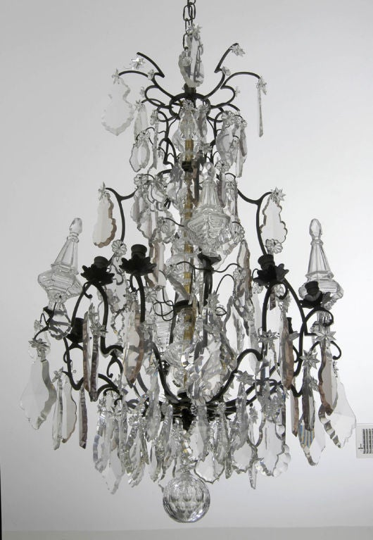 Large Louis XV style birdcage-form bronze and crystal eight-light chandelier with large shaped decorative clear and pale amber-colored drops, four large glass capitals, large cut-glass ball. It has been electrified.