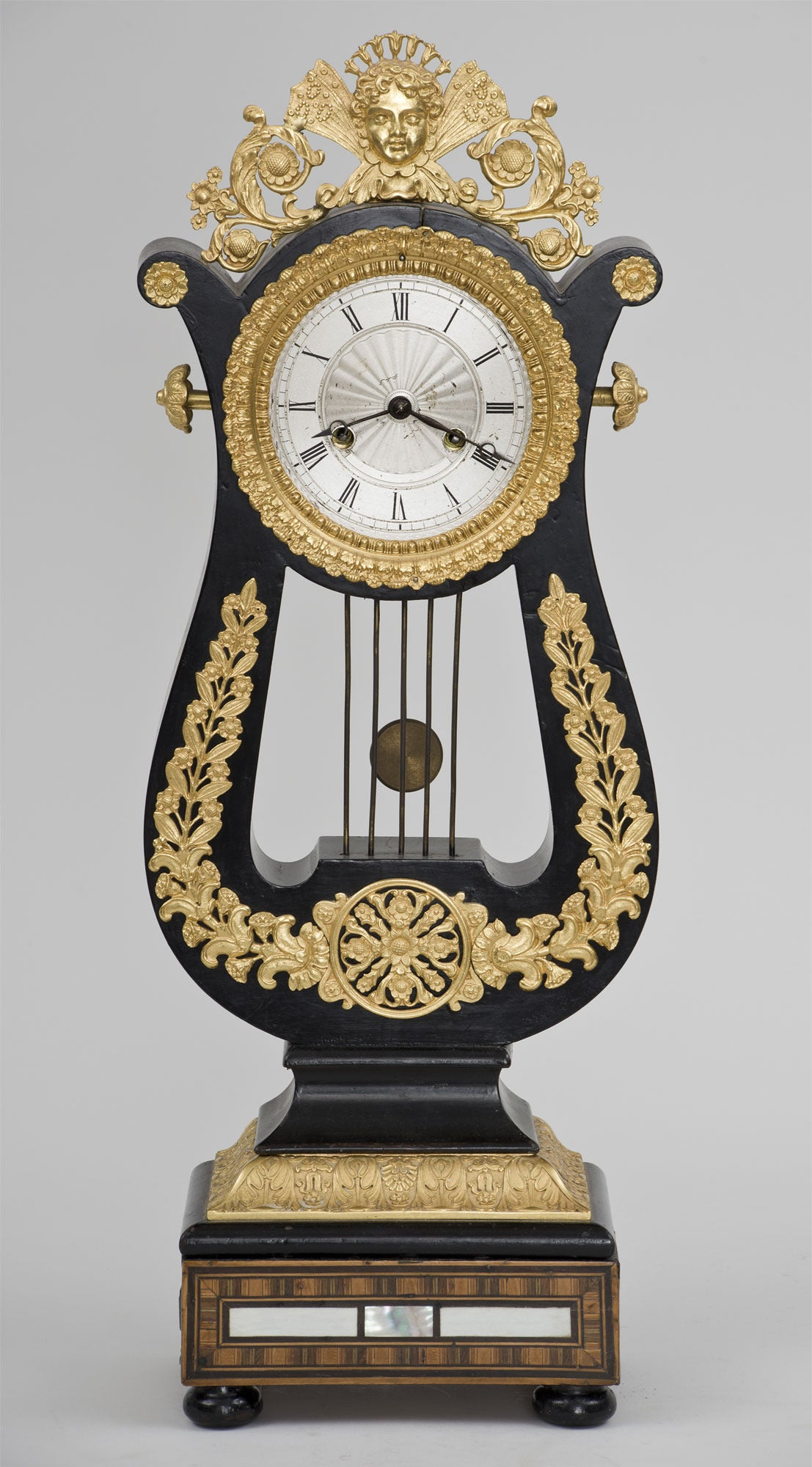 French lyre-shaped ebonized gilt bronze mantel clock with eight-day movement, silvered Roman chapter disc, bell striking on the hour and the half hour. The case with foliate and figural ormolu mounts, the base inlaid with rosewood and