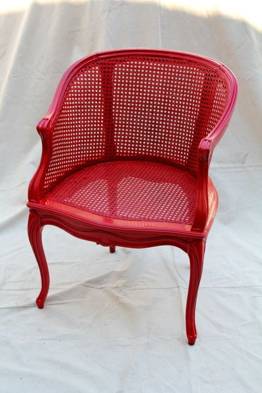 A nice painted french cane chair. Solidly built and newly painted a bright red. It is sturdy and features some nice carved details.