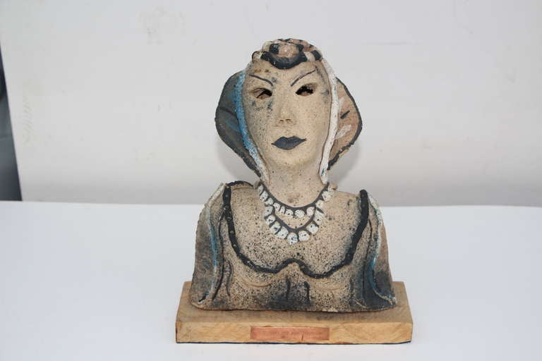 A very unusual ceramic or terracotta with hollow eyes that bears a copper plaque on the base that reads