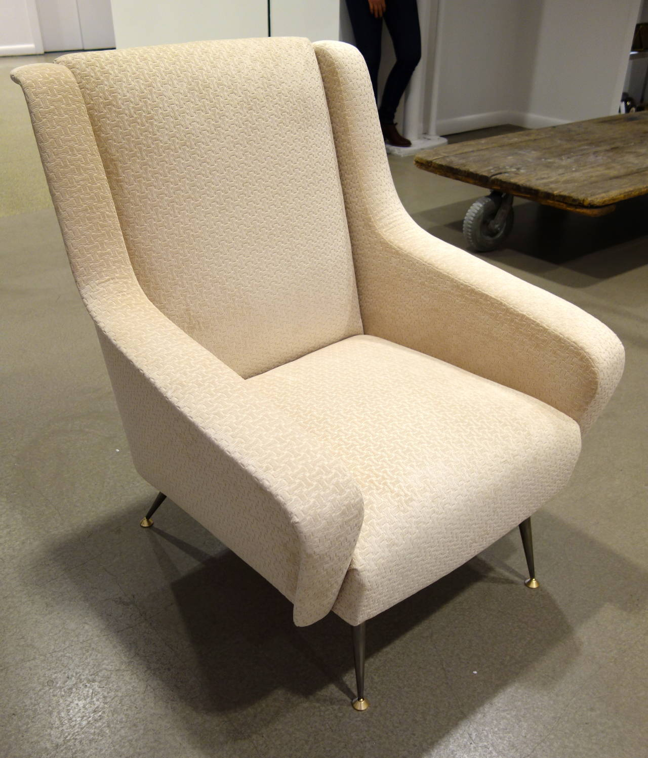A pair of Mid-Century Italian lounge or armchairs with sculptural flat armrests, tight backs and seats resting on metal legs with brass capped feet newly upholstered in pale mushroom geometric patterned chenille. Image 6 shows the truest color and a