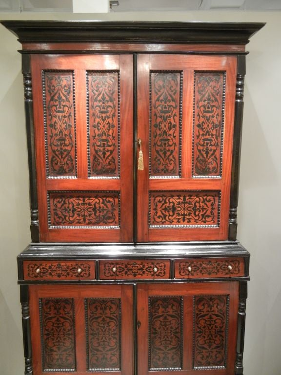 A colonial Dutch mahogany three-sectioned cabinet with an all-over design of inlaid ebony, the surface with a series of rectangular and horizontal coffered panels with beaded trim, the upper section opening to three shelves, the middle section