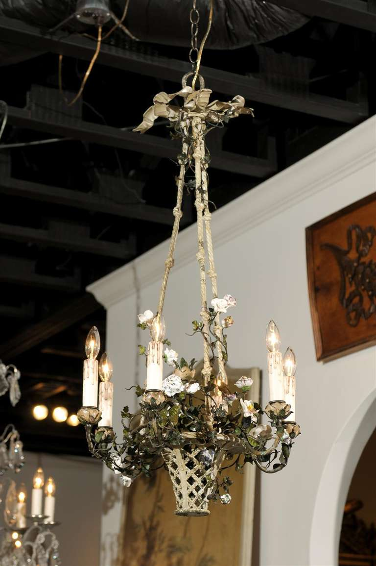 A French Rococo style bronze six-light basket chandelier from the late 19th century, with painted porcelain flowers. Born in France during the last quarter of the 19th century, this Rococo style chandelier features a charming pastoral theme. The