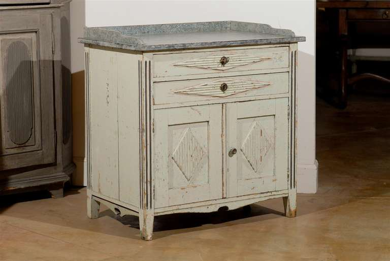 A Swedish Gustavian style painted wood buffet with three-quarter gallery, two drawers and two doors from the late 19th century. This Swedish buffet features a rectangular grey top surrounded with a three-quarter gallery, sitting above two drawers.