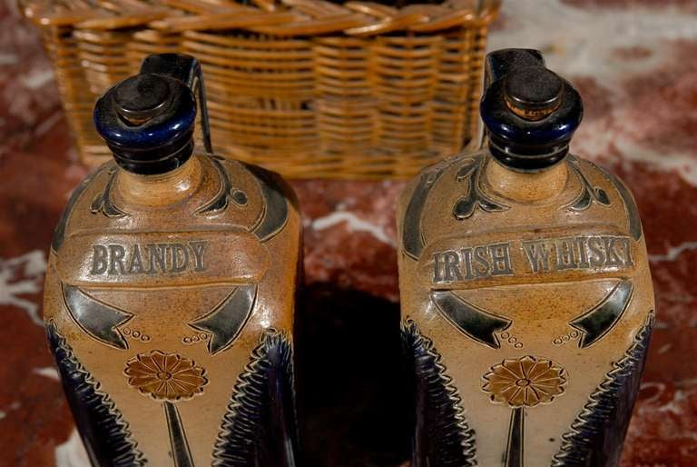 19th Century Two Victorian English Pottery Decanters in Tantalus-Inspired Wicker Basket For Sale