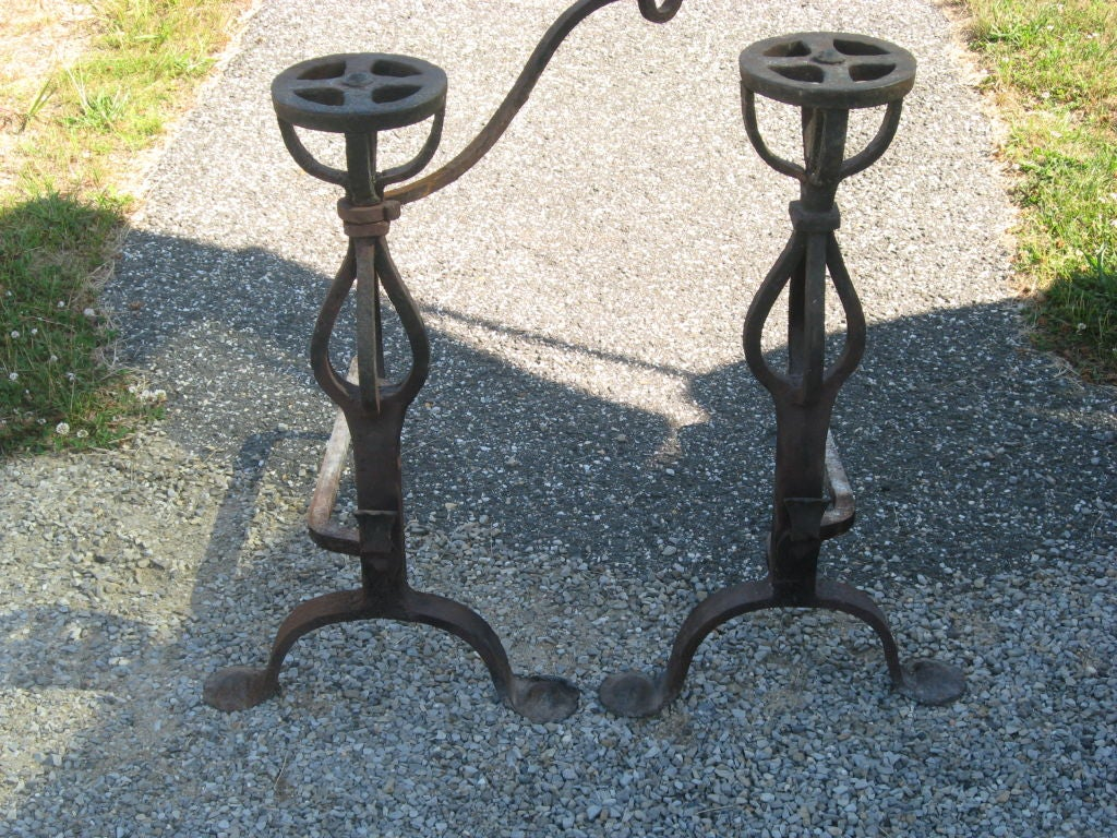 Vintage pair of hand-forged iron andirons with pot holder.