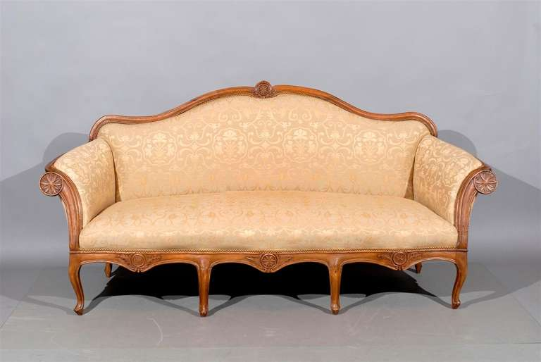 18th century Venetian walnut canape in the Rococo style with carved arched back, scrolled arms, shaped apron and new upholstery. 