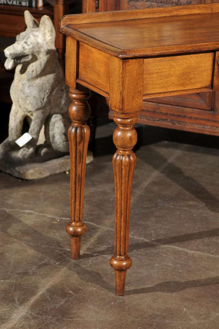 English 1880s Oak Console Table with Single Drawer, Shield Motif and Reeded Legs For Sale 3