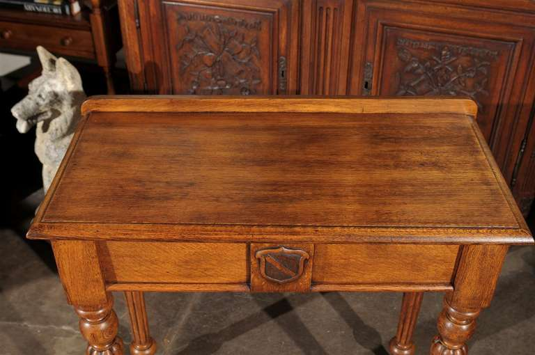 An English oak console table with single drawer, shield motif and reeded legs from the late 19th century. This English console table features a rectangular top with beveled edges, accented by a solid wooden gallery in the back. The single dovetailed